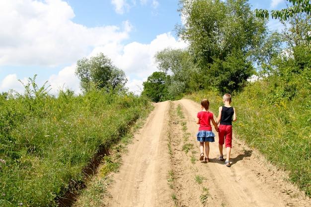 Chłopiec i dziewczynka chodzą po polnej drodze w słoneczny letni dzień. dzieci trzymając się za ręce razem, ciesząc się zabawą na zewnątrz Premium Zdjęcia