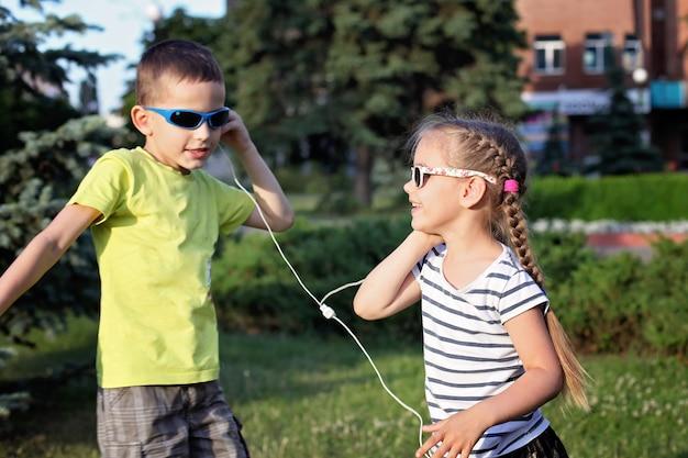 Chłopiec i dziewczynka słuchania muzyki w słuchawkach i taniec Premium Zdjęcia