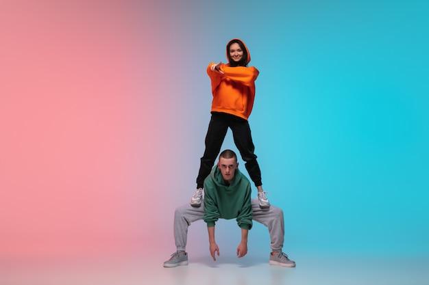 Chłopiec I Dziewczynka Tańczy Hip-hop W Stylowe Ubrania Na Gradientowym Tle W Sali Tanecznej W świetle Neonu. Darmowe Zdjęcia