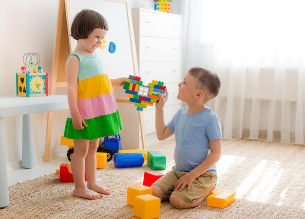 Chłopiec i dziewczynka trzymają serce wykonane z plastikowych bloków. brat i siostra bawią się razem Premium Zdjęcia