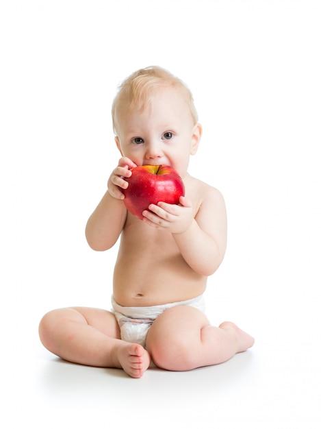 Chłopiec Je Czerwonego Jabłka, Odizolowywającego Na Bielu Premium Zdjęcia
