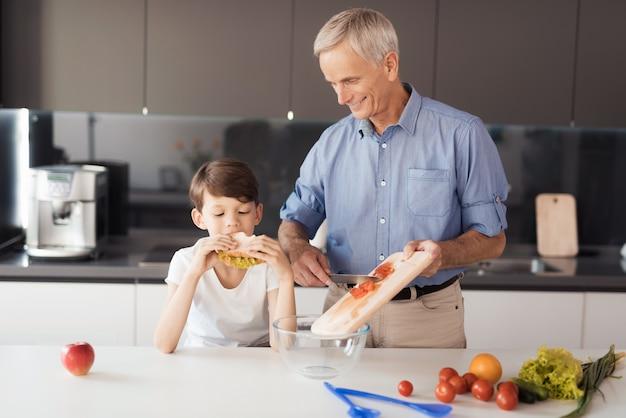 Chłopiec Je Kanapkę Z Sałatką. Premium Zdjęcia
