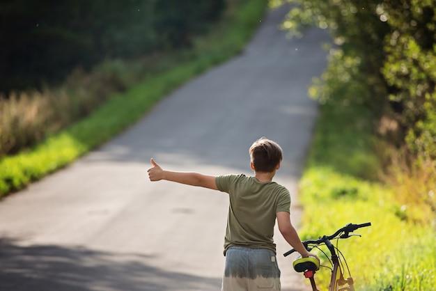 Chłopiec Jedzie Autostopem. Nastolatek Na Rowerze Próbuje Złapać Przejeżdżający Samochód Na Podróż. Premium Zdjęcia