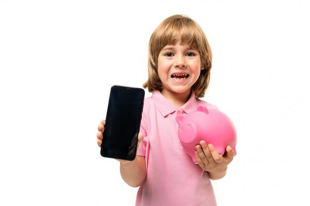 Chłopiec Kaukaski Teeanger Trzyma Telefon W Jednej Ręce I Różowa świnia Skarbonka W Drugiej Ręce Na Białej ścianie Premium Zdjęcia