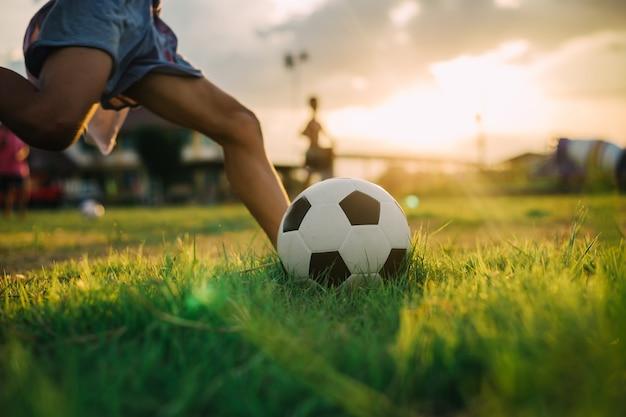 Chłopiec kopie piłkę bosą stopą podczas gry w piłkę nożną ulicy na polu zielonej trawie Premium Zdjęcia