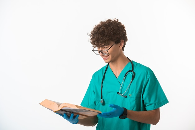 Chłopiec Kręcone Włosy W Mundurze Medycznym I Maski, Czytając Starą Książkę I Uśmiechając Się. Darmowe Zdjęcia