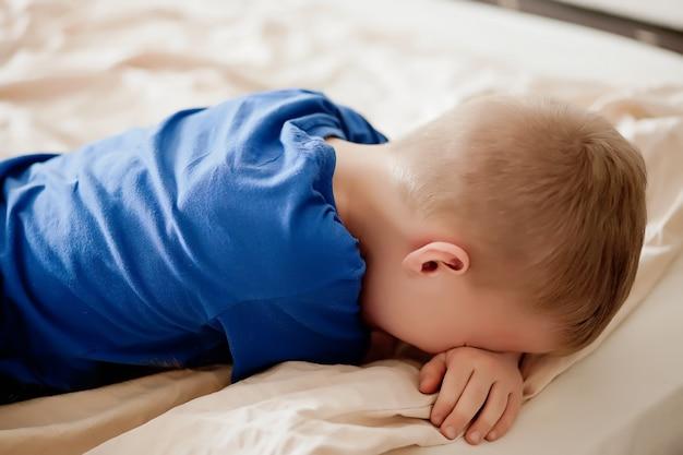 Chłopiec Leży Na łóżku Odwrócony Plecami I Płacze. Premium Zdjęcia