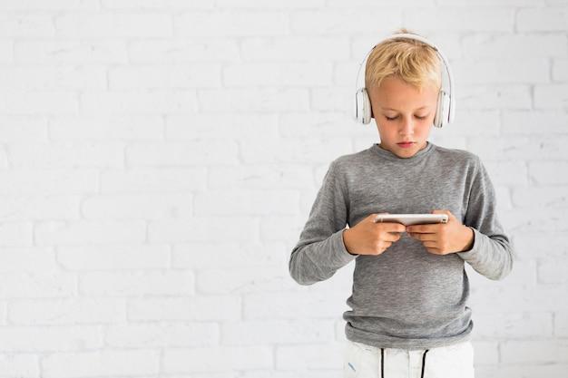 Chłopiec ma zabawę z smartphone i słuchawkami Darmowe Zdjęcia