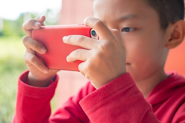 Chłopiec mienia smartphone w horyzontalnej pozyci Premium Zdjęcia