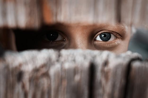 Chłopiec patrzy przez szczelinę w płocie Premium Zdjęcia