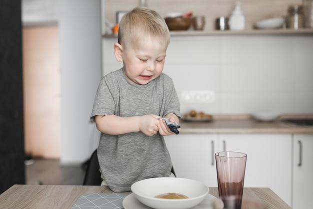 Chłopiec pozycja na krześle gniesie paczkę w pucharze Darmowe Zdjęcia