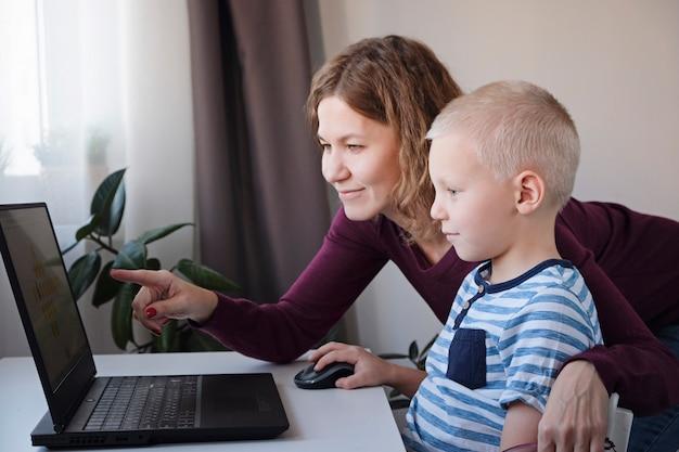 Chłopiec Pracuje Na Komputerze Wraz Z Jego Mamą W Domu. E-lekcje, Edukacja Dla Dzieci. Premium Zdjęcia