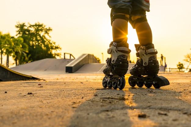 Chłopiec rollerblading publicznie parkuje z ochrony wyposażeniem na zmierzchu tle Premium Zdjęcia