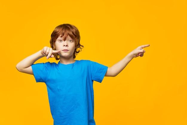 Chłopiec Rude Włosy Niebieski T-shirt żółte Na Białym Tle Piegi I Wskaż Palcem W Bok, ładna Buźka Premium Zdjęcia