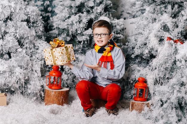 Chłopiec siedzący na podłodze nie lubi prezentu świątecznego Premium Zdjęcia