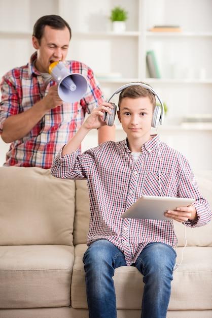 Chłopiec siedzi na kanapie i za pomocą cyfrowego tabletu. Premium Zdjęcia