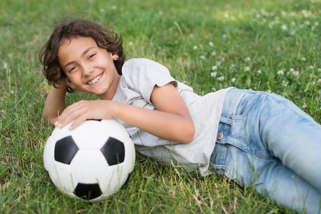 Chłopiec Siedzi W Trawie Z Piłki Nożnej Darmowe Zdjęcia