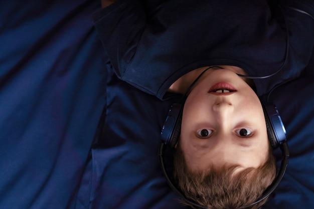 Chłopiec słuchania muzyki w słuchawkach leżąc w łóżku Premium Zdjęcia
