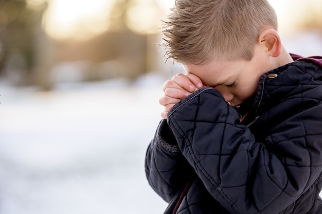 Chłopiec Stojący Z Zamkniętymi Oczami I Modlący Się Darmowe Zdjęcia