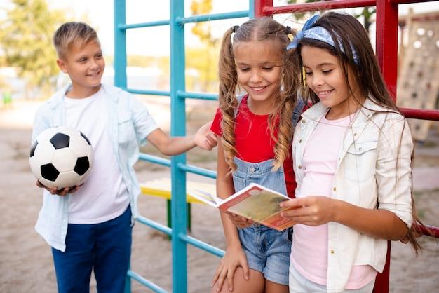 Chłopiec Trzyma Piłkę Podczas Gdy Dziewczyny Czytają Książkę Darmowe Zdjęcia