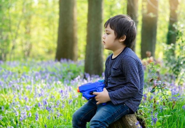 Chłopiec trzyma plastikowego pistoletu wodnego Premium Zdjęcia