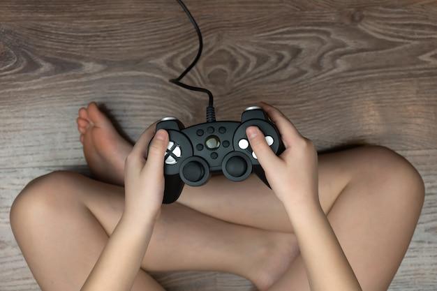 Chłopiec Trzyma W Dłoni Gamepad Z Konsoli Do Gier Wideo Premium Zdjęcia