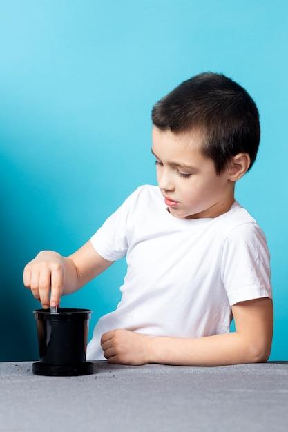 Chłopiec Używa Probówki, Aby Zrobić Dziury W Ziemi, Aby Zasadzić Nasionko I Wyhodować Na Stole Roślinę Domową Premium Zdjęcia