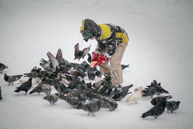Chłopiec W Ciepłe Zimowe Ubrania Karmi Gołębie W Parku Miejskim Premium Zdjęcia