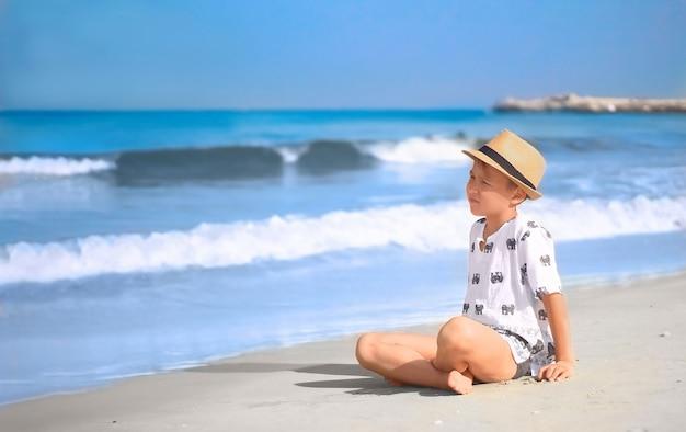 Chłopiec W Kapeluszu Siedzi Na Plaży O Poranku, Patrząc Na Fale Premium Zdjęcia