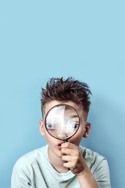 Chłopiec W Lekkiej Koszulce, Patrząc W Duże Szkło Powiększające Premium Zdjęcia