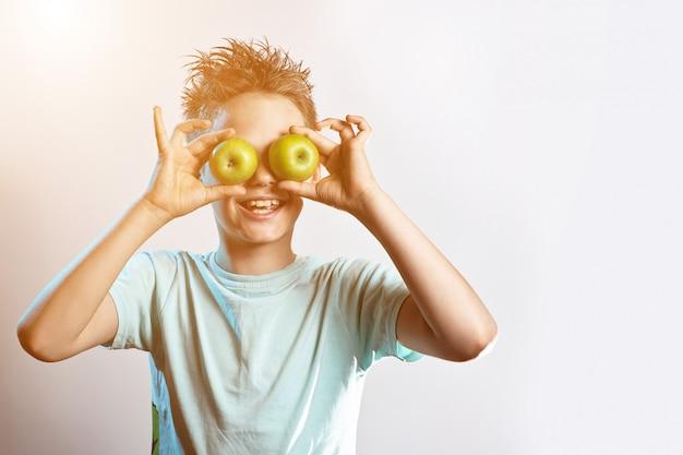 Chłopiec W Niebieskiej Koszulce Przyłożył Do Oczu Dwa Zielone Jabłka I Się śmieje Premium Zdjęcia