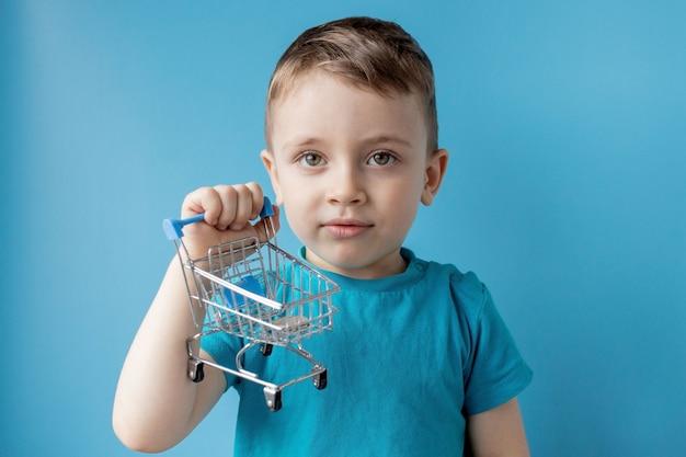 Chłopiec W Niebieskiej Koszulce Trzyma Koszyk I Monetę Na Niebieskim Tle. Koncepcja Zakupów I Sprzedaży. Premium Zdjęcia