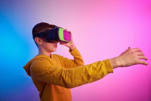 Chłopiec W Okularach Wirtualnej Rzeczywistości Na Kolorowym Tle Premium Zdjęcia