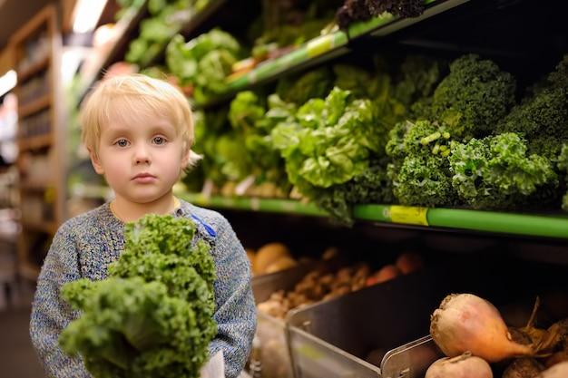 Chłopiec W Supermarkecie Wybiera świeżego Organicznie Kale Premium Zdjęcia