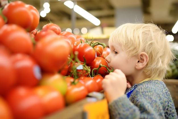 Chłopiec W Supermarkecie Wybiera świeżych Organicznie Pomidory Premium Zdjęcia