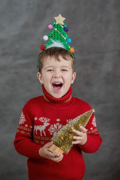 Chłopiec W świątecznym Swetrze I Obręczy Choinki Z Małą Choinką. Premium Zdjęcia