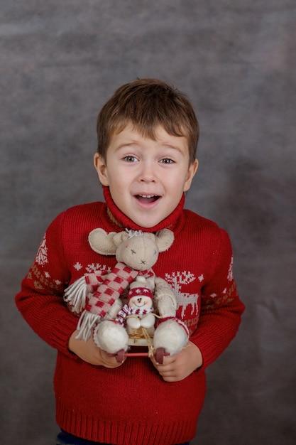 Chłopiec W świątecznym Swetrze Z świąteczną Zabawką Jelenia. Premium Zdjęcia