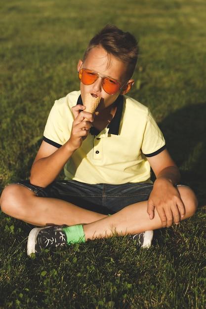 Chłopiec W żółtej Koszulce Siedzi Na Trawie I Je Lody. Wygląd Azjatycki Premium Zdjęcia