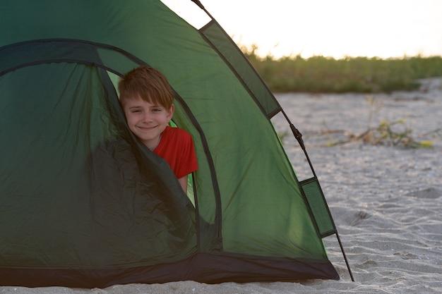 Chłopiec Wyglądający Z Namiotu Turystycznego. Aktywne Wakacje. Kemping. Premium Zdjęcia