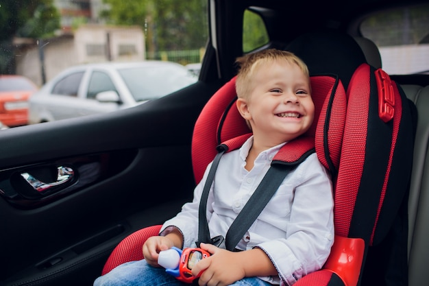 Chłopiec Z Kędzierzawym Włosy Obsiadaniem W Dziecięcym Samochodowym Siedzeniu Z Zabawkarskim Samochodem W Rękach Premium Zdjęcia