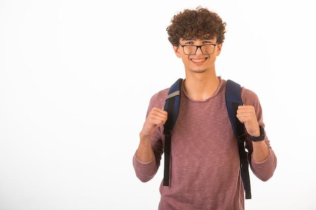 Chłopiec Z Kręconymi Włosami W Okularach Optique Trzyma Plecak I Jest Gotowy Do Podróży. Darmowe Zdjęcia