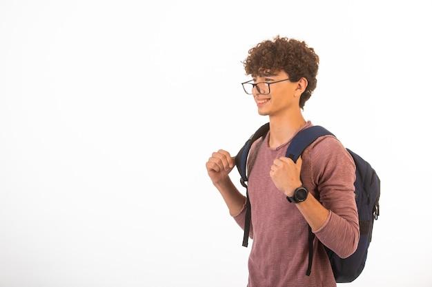 Chłopiec Z Kręconymi Włosami W Okularach Optique Trzymający Plecak Jest Pewny Siebie I Zmotywowany. Darmowe Zdjęcia