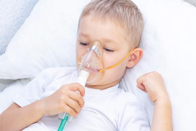 Chłopiec Z Maską Inhalatora. Problemy Z Oddychaniem W Astmie. Chłopiec Z Maską Inhalacyjną Leży W łóżku I Oddycha Adrenaliną. Premium Zdjęcia