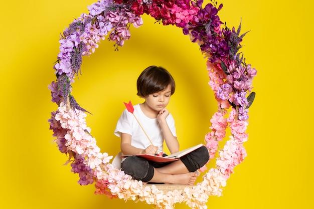 Chłopiec Z Przodu Czytający Książkę W Białej Koszulce Siedzący Na Kwiatku Stał Na żółtej Przestrzeni Darmowe Zdjęcia