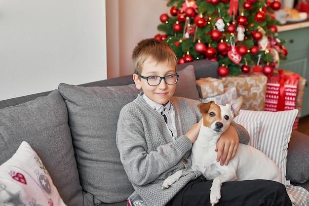 Chłopiec z psem blisko choinki na bożych narodzeniach Premium Zdjęcia