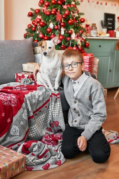 Chłopiec z psem w pobliżu choinki na tle bożego narodzenia Premium Zdjęcia