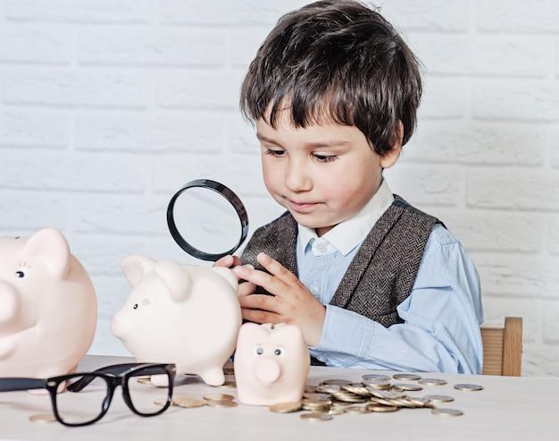 Chłopiec z świniowatym prosiątko bankiem Premium Zdjęcia