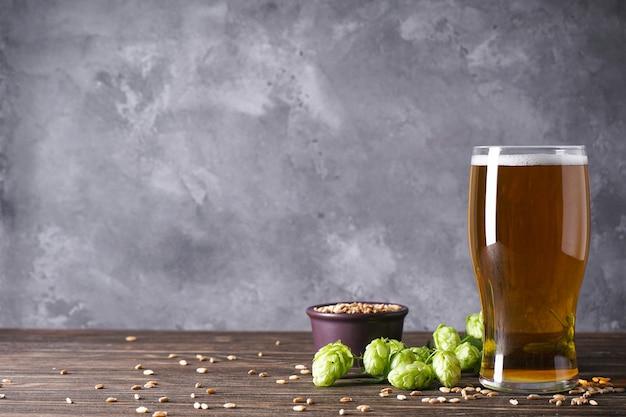 Chmiel I Szklanka Jasnego Piwa Na Szarej Przestrzeni, Miejsce Na Tekst. Premium Zdjęcia