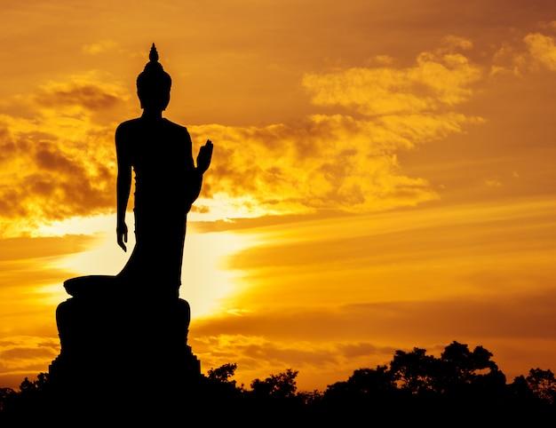 Chodząca buddha statuy sylwetka przy zmierzchem Premium Zdjęcia