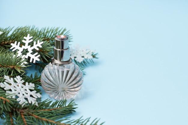 Choinka i butelka perfum z bliska na niebieskim, copycopyspace Premium Zdjęcia
